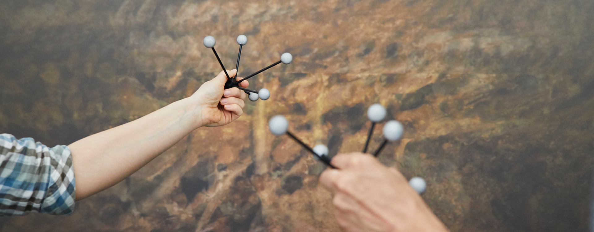 Molecule models are held up by two hands